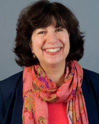 Portrait of Kathie Friedman-Kasaba smiling, with shoulder-length hair, wearing a colorful scarf