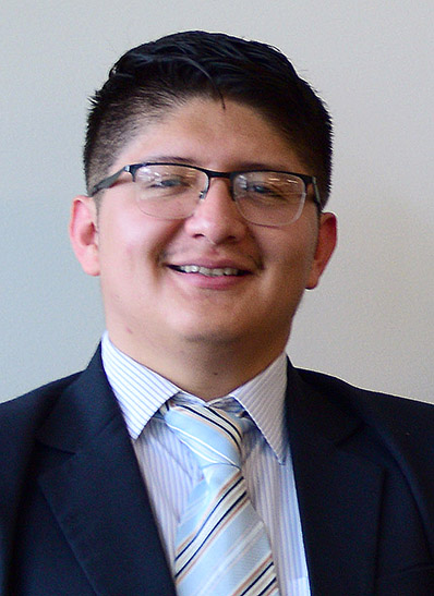 Portrait of Pablo smiling, wearing glasses, in suit and tie