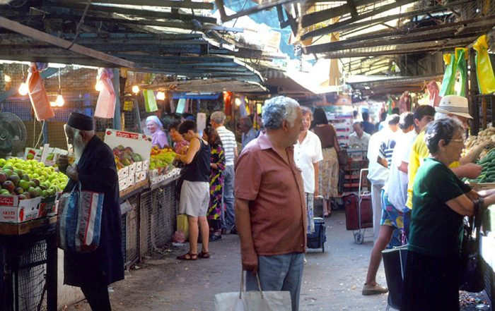 Shoppers purchase produce at stalls in a covered market