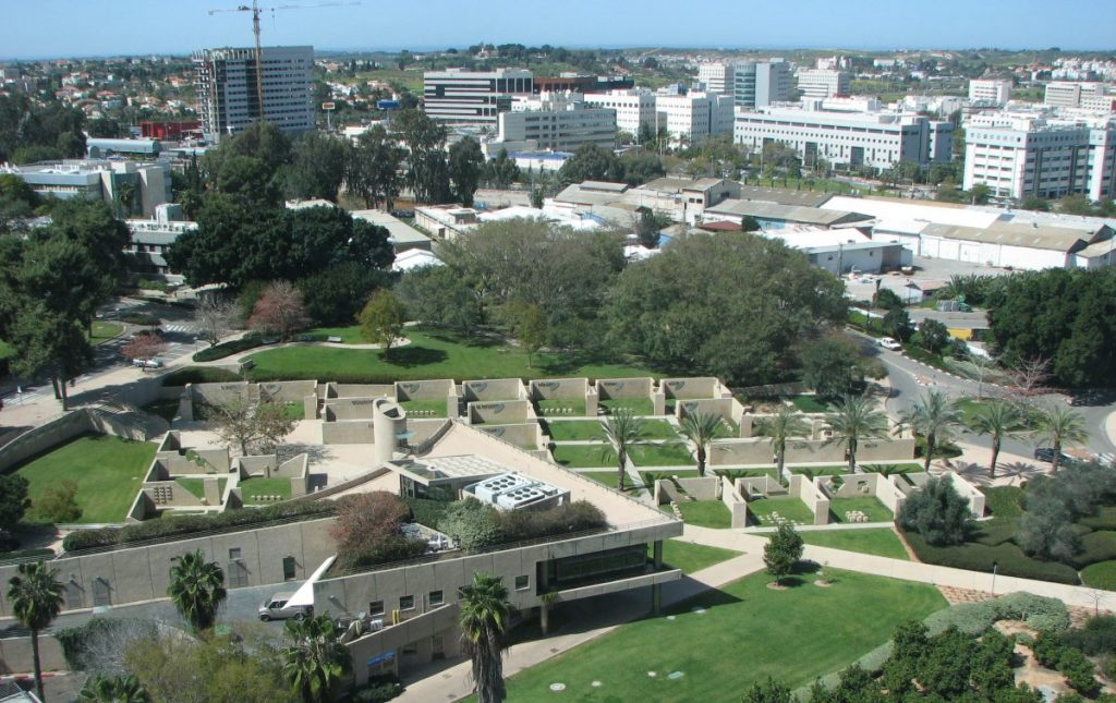 An overhead view of the Institute grounds, which include a large lawn and an expansive garden with palm trees and walled-off sections. The Institute is a two-story, white-gray modern building with a flat roof.