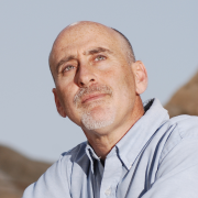 A portrait of Alon Tal gazing upwards optimistically, wearing a button-down shirt, desert hiills in the back