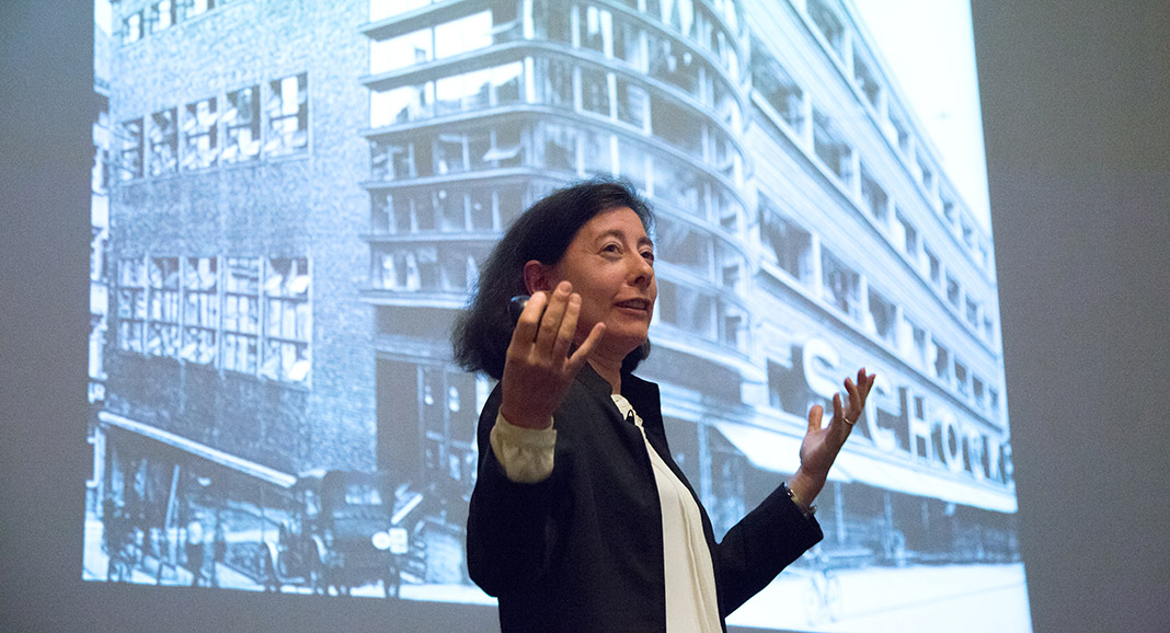 Lecturer Adina Hoffman stands in front of a slide of a black-and-white photo of a high-rise building