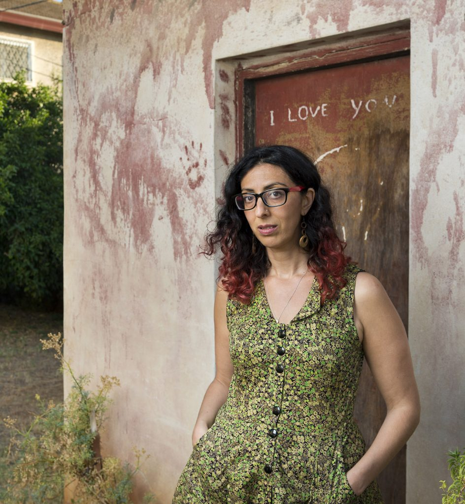 "Portrait of Ayelet Tsabari looking serious, hands in pockets of a summer dress, standing in front of the door of a rustic building that has ""I love you"" scrawled on it"