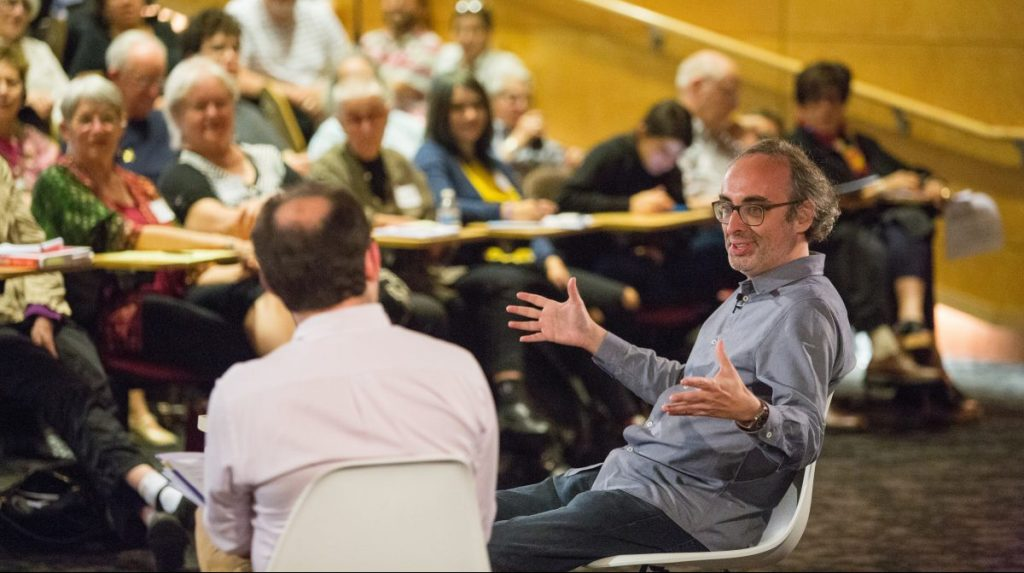 Seated, author Gary Shteyngart talks with Professor Sasha Senderovich in front of a large audience