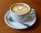 A cappuccino in cup and saucer with a heart-shaped design on top