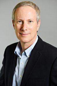 Portrait of Derek Penslar, smiling slightly, wearing a button-up shirt and outer jacket