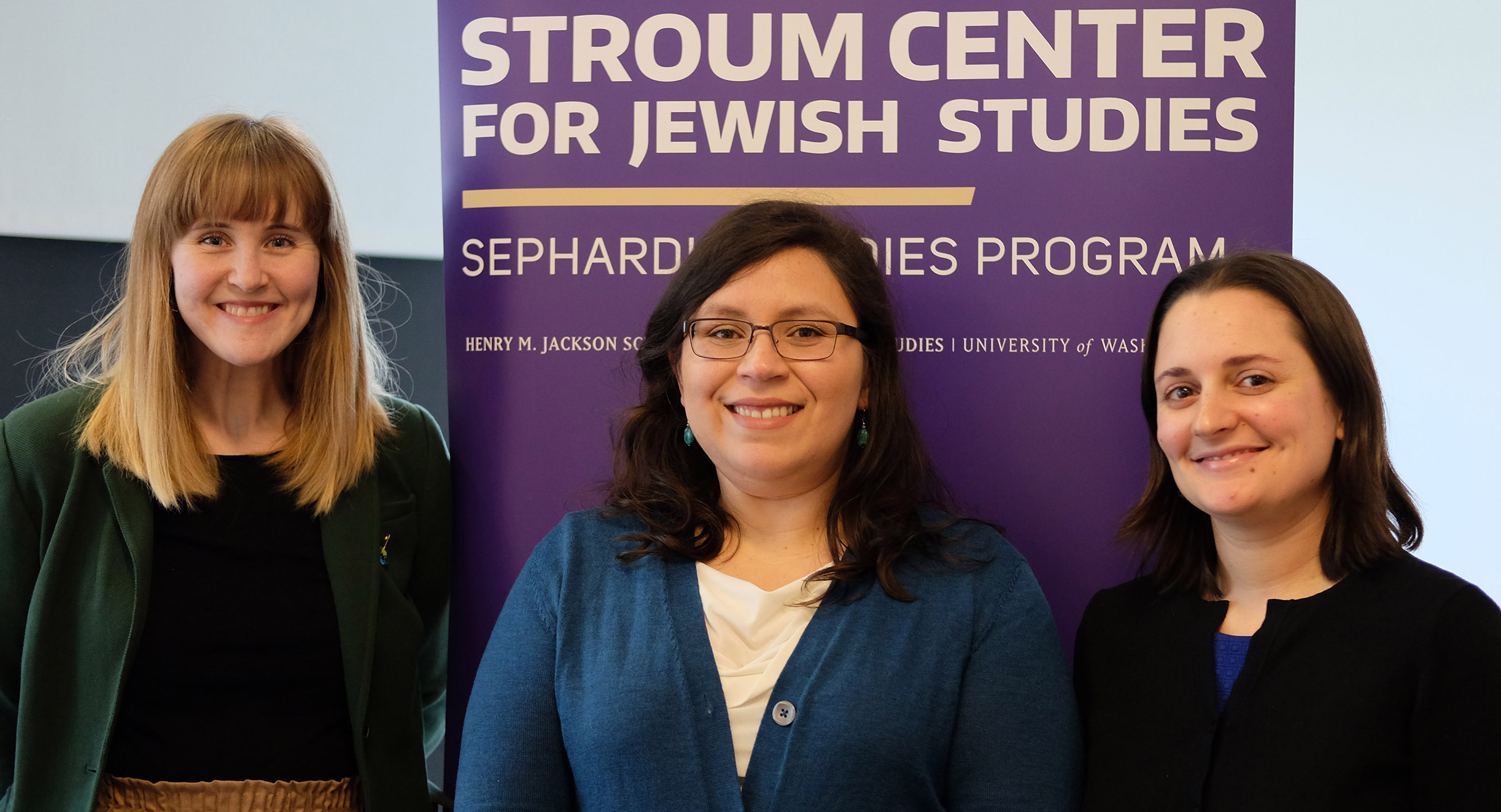 Three graduate fellows smile while standing in front of a purple Stroum Center banner after a research presentation