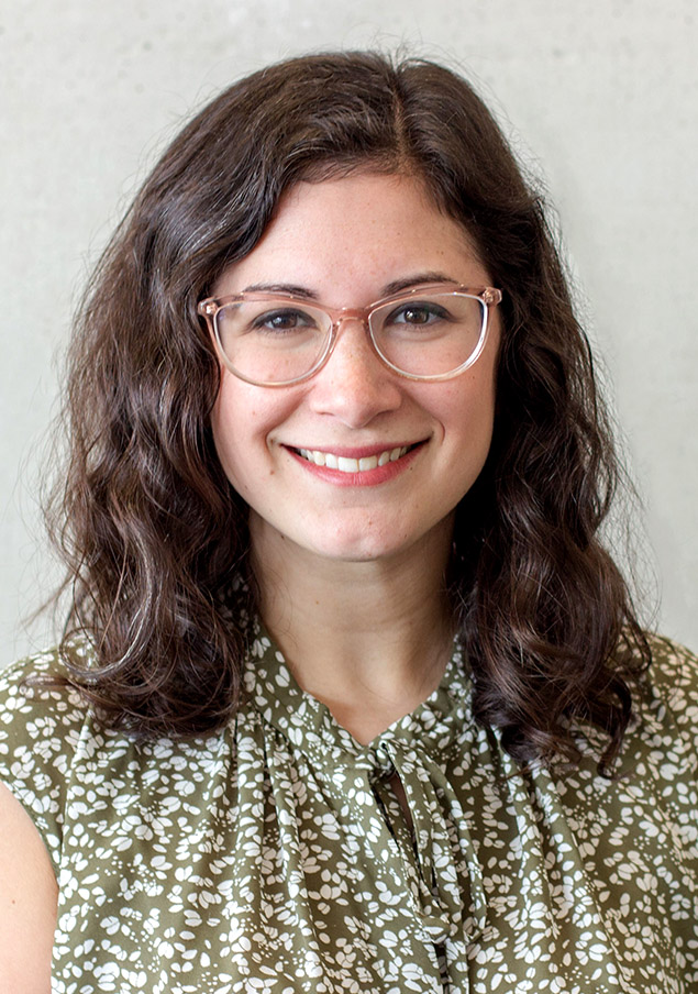 Portrait of Shari Rabin, smiling, wearing glasses and a formal blouse