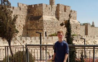 Alex Peterson stands in front of a railing, Jerusalem's ancient city wall, mosque minaret and blue sky in the background