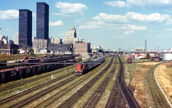 Color photograph shows a train running along rails set up alongside Toronto, identifiable from several skyscrapers and historic large buildings, under blue skies