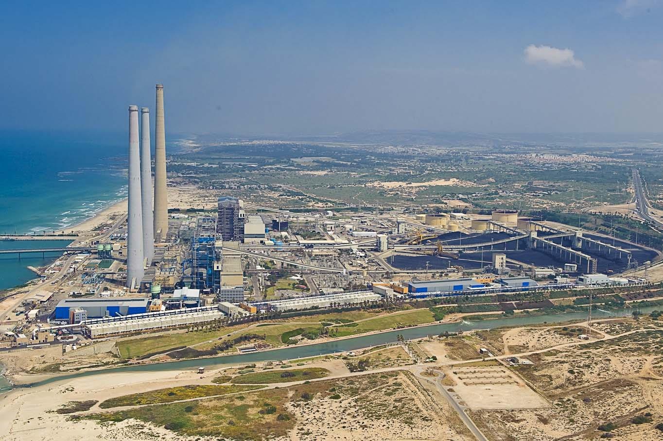 Aerial photograph of a large desalination complex in Israel, situated between sea, a green populated area, and desert