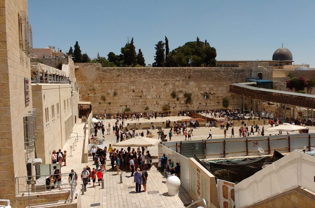 The busy plaza alongside the Wailing Wall, blue sky and sun overhead