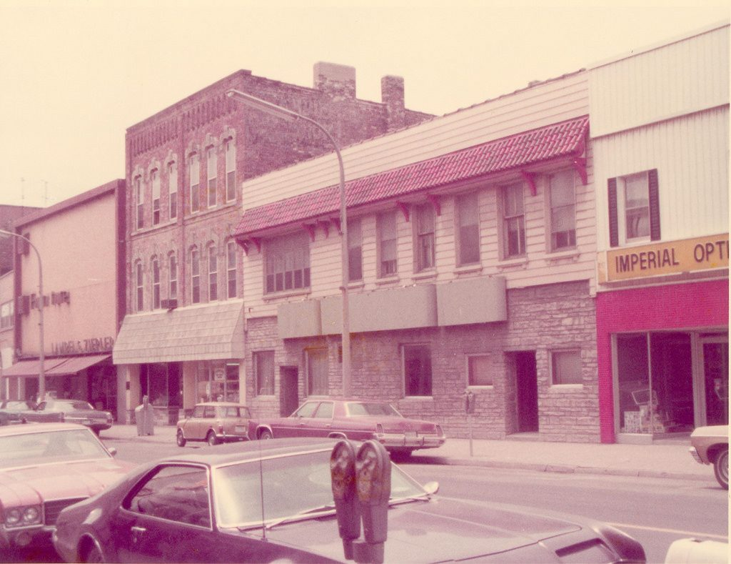Aged color photograph showing a series of vintage storefronts, some of brick