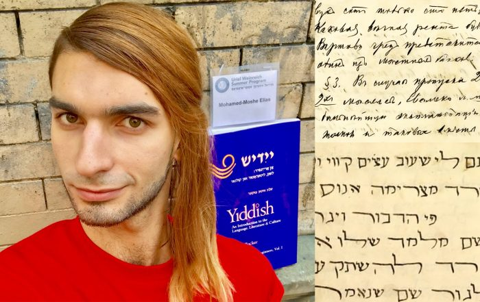 Photo of author Mohamed Elias looking at the camera, with a nametag and Yiddish textbook behind him and written Yiddish and Judeo-Arabic text at the right