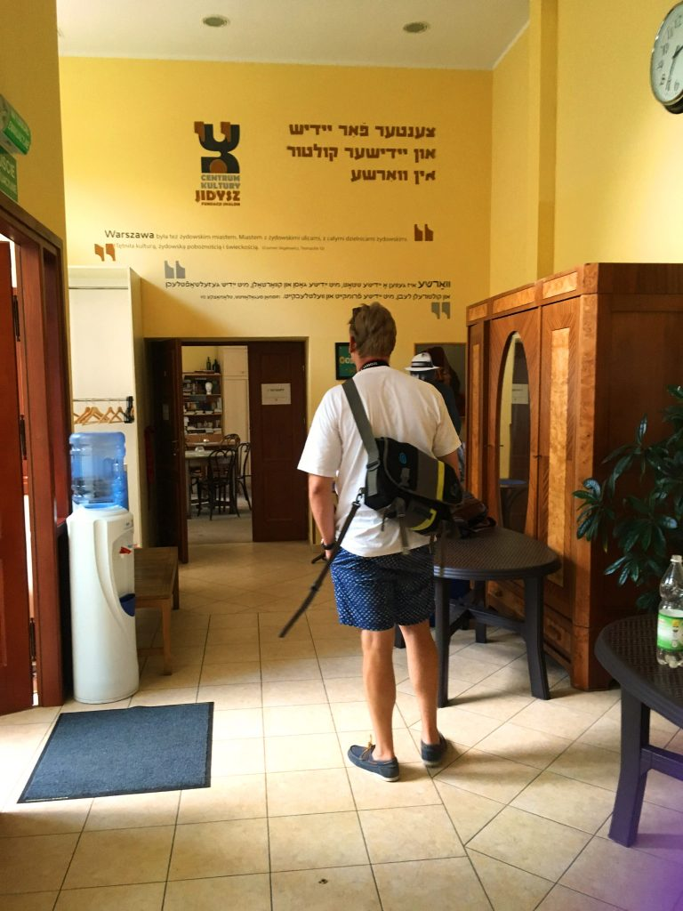 One visitor stands in the middle of a hallway with a high ceiling in POLIN, reading lines in Yiddish and Polish printed above a doorway