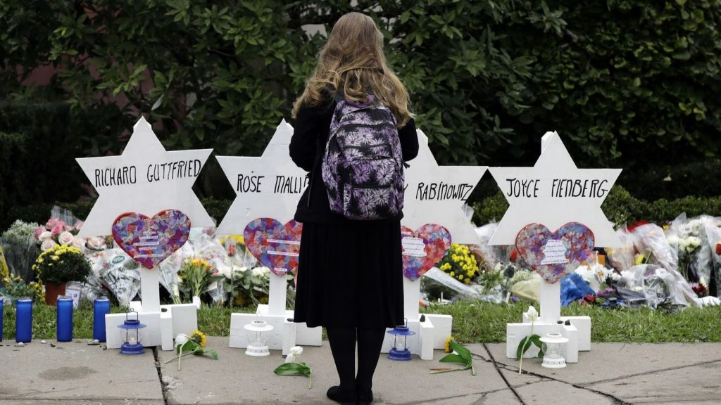 Woman in black, wearing a backpack stands in front of markers bearing the names of synagogue shooting victims