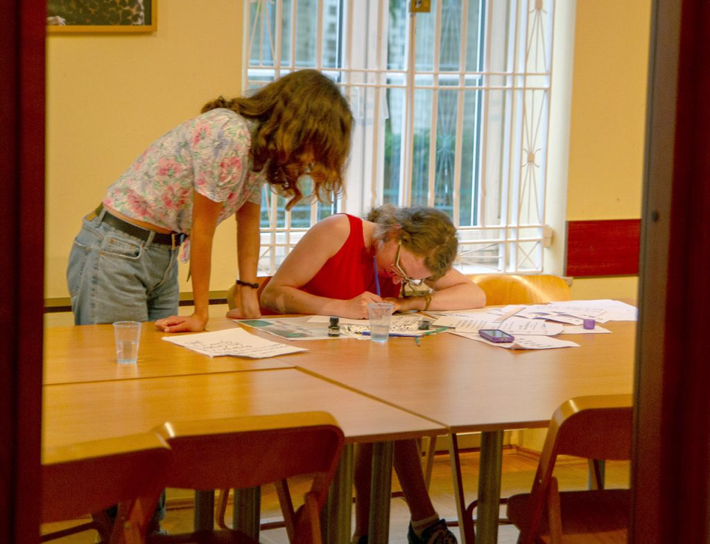 Two students study hunch over a table, looking at papers intently