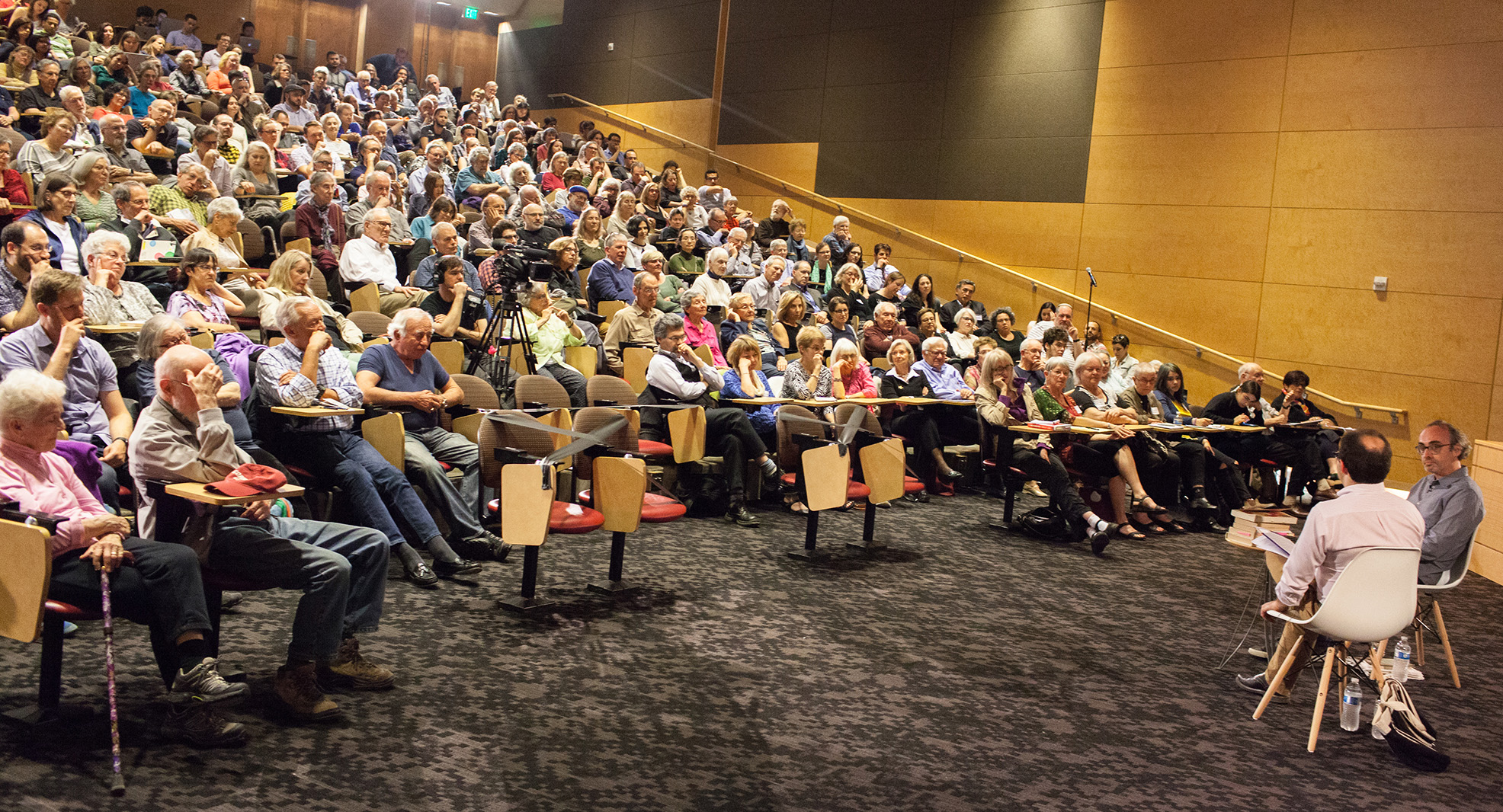 A crowded lecture hall at the University of Washington campus, with two speakers in discussion at the front