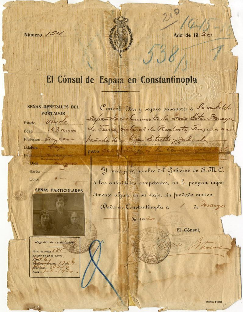 "A historic passport from ""El Cónsul de España de Constantinopla"" on yellowed paper, with printed fields and handwritten details in script and a black-and-white photograph of Ester and daughters at the bottom left"