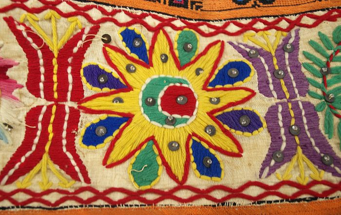 A colorful embroidered cloth with a flower-like yellow starburst surrounding a crescent moon in the middle and red and purple floral pattern on either side