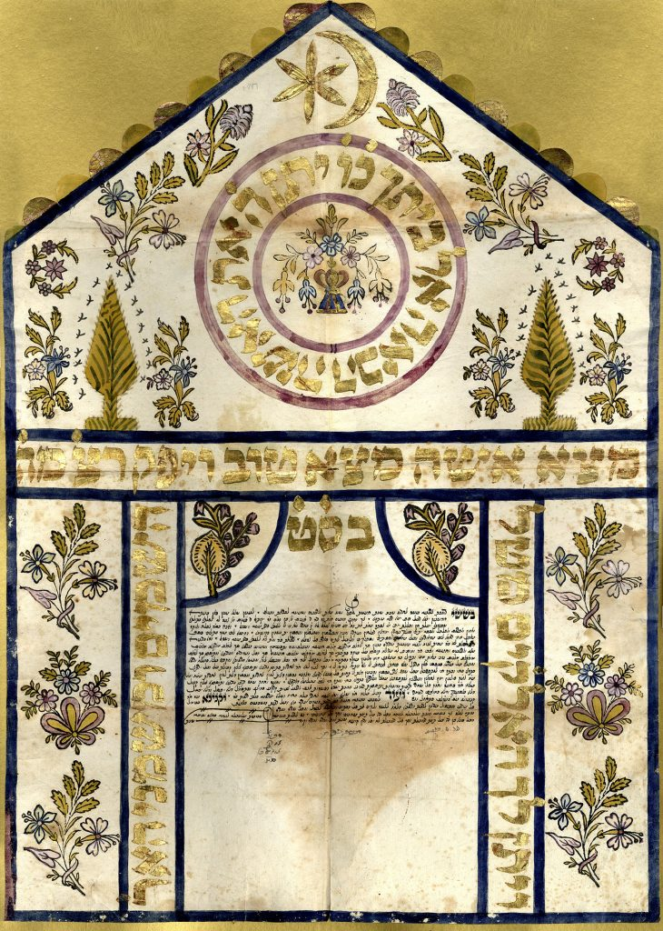An ornate ketubah with handwritten Hebrew contract text, surrounded by flowers, leaves, and golden Hebrew calligraphy. A golden crescent moon and star sits at the top.