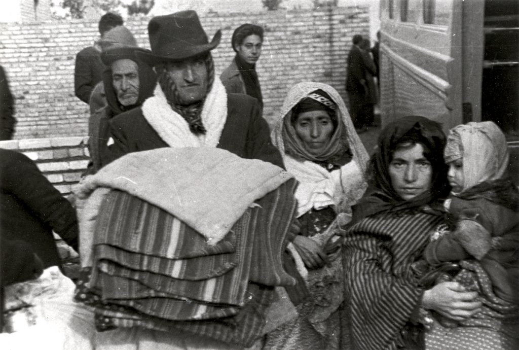 A black-and-white photograph showing a family of Kurdish Jews dressed for cold weather, wearing hats and scarves