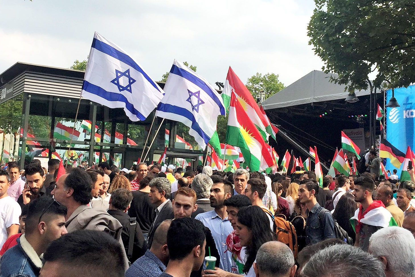 Photograph shows a crowded square full of Kurdish people of various ages waving red, green and white Kurdish flags along with white and blue Israeli flags