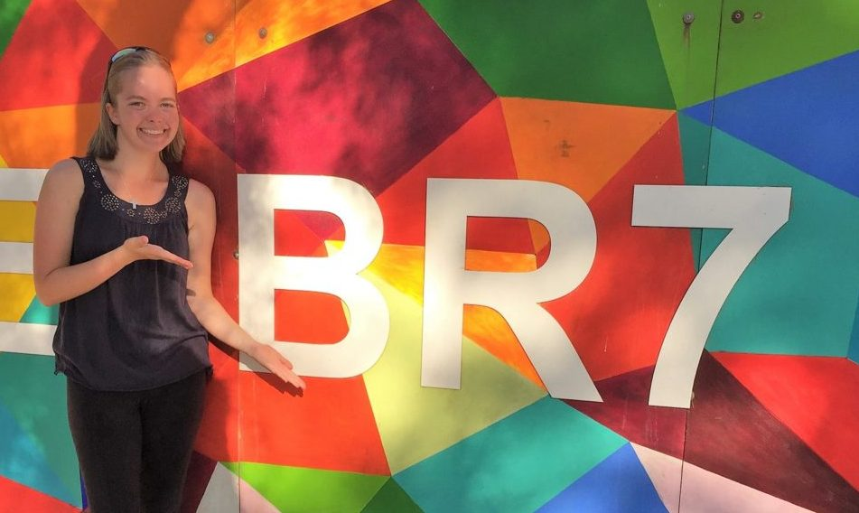 "Marissa Gaston standing in front of a colorful mural of geometric shapes that has ""BR7"" painted over it in large white block letters. Marissa smiles and gestures to the letters proudly"