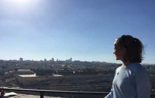 Student Marissa Gaston looks out over Jerusalem under a blue sky