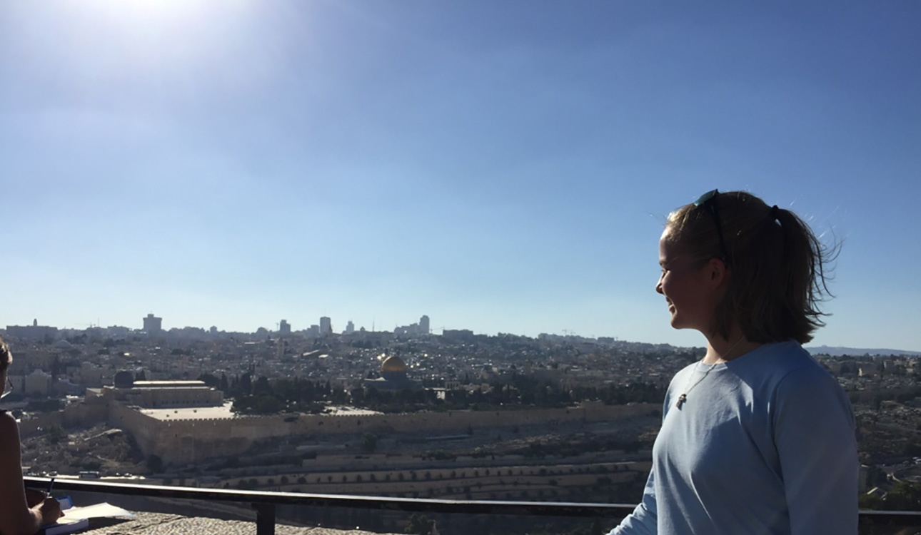 In profile, Marissa Gaston looks down at the city of Jerusalem, smiling, a vast, bright blue sky overhead