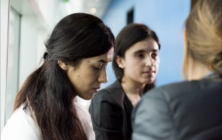 Photo showing two somber-looking Kurdish women in a hallway in discussion with someone off-camera