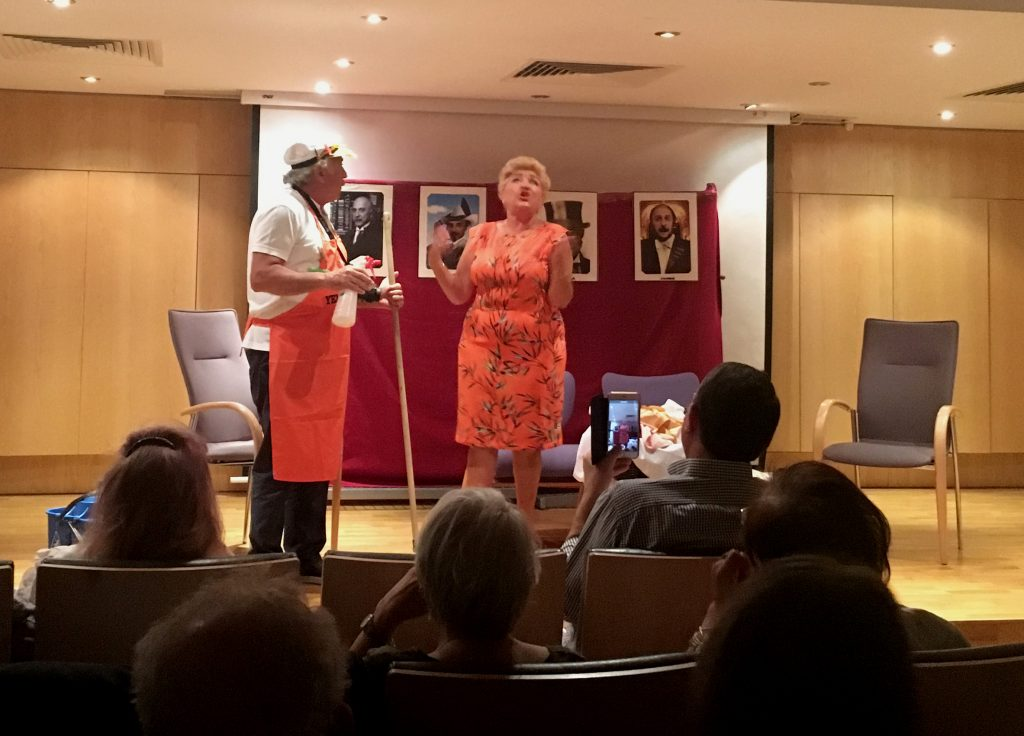 Onstage, a middle-aged woman in a pink floral dress looks upset and an older man in a cap and red apron looks on