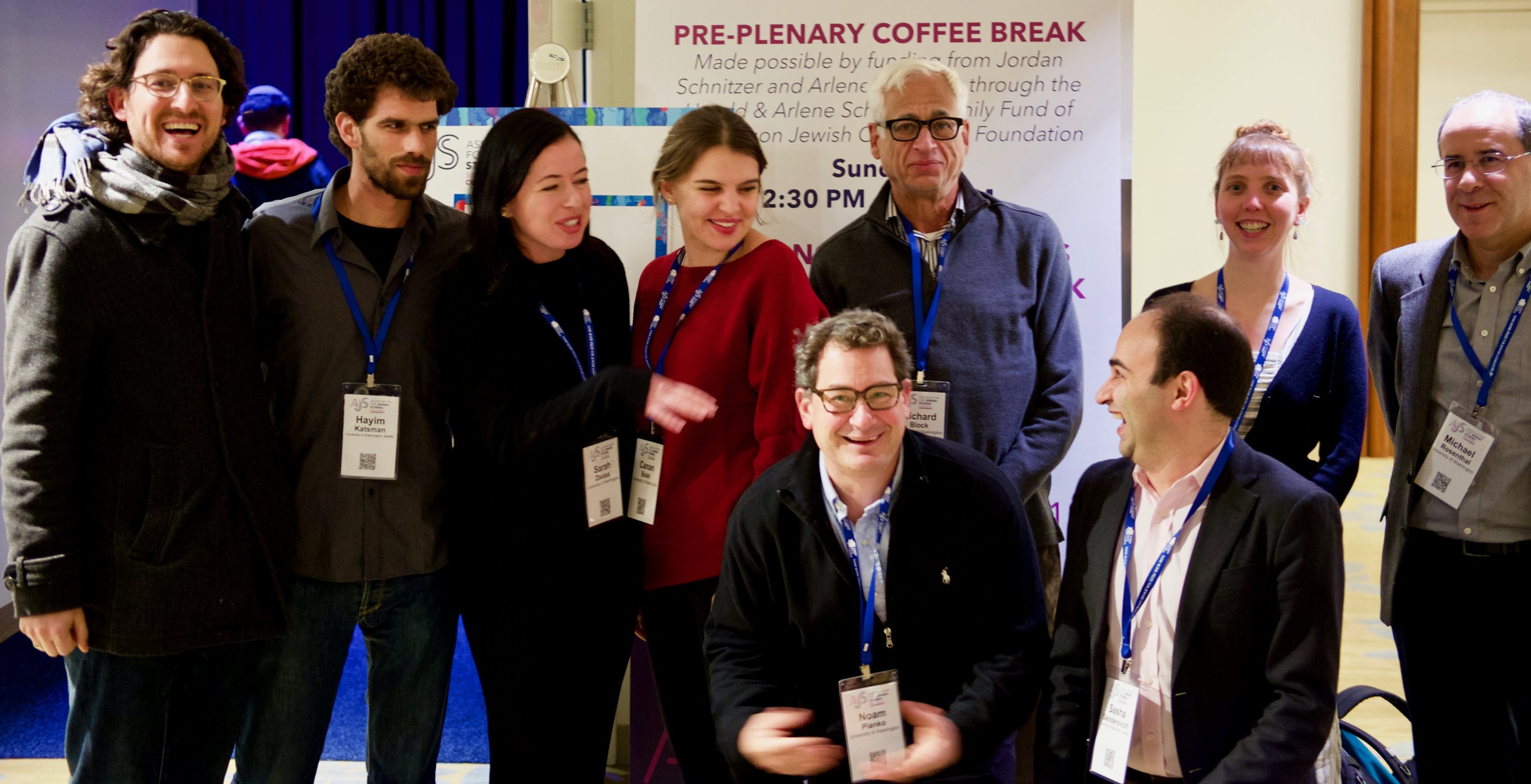 "Group photo of several students and faculty members standing or kneeling in a conference center room. Sign in back reads ""Pre-plenary coffee break."""