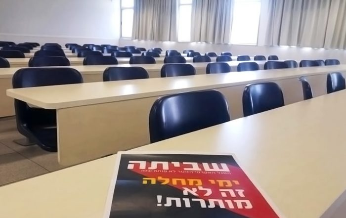 An empty classroom with long tables and seats, all empty. A black and red poster in Hebrew reading