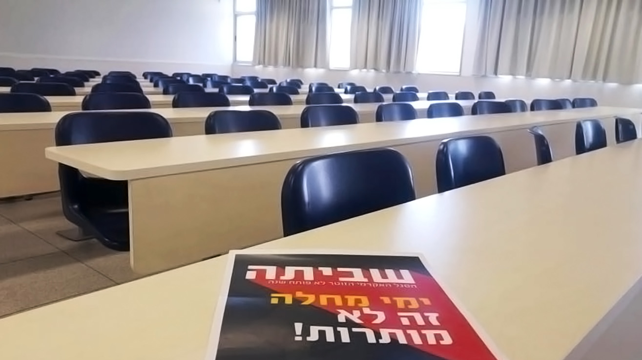 "An empty classroom with long tables and seats, all empty. A black and red poster in Hebrew reading ""Strike!"" sits on the front table."