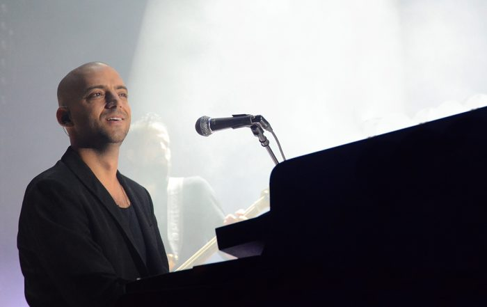 Idan Raichel smiles and looks out at the crowd in concert, playing the piano with a microphone close by.
