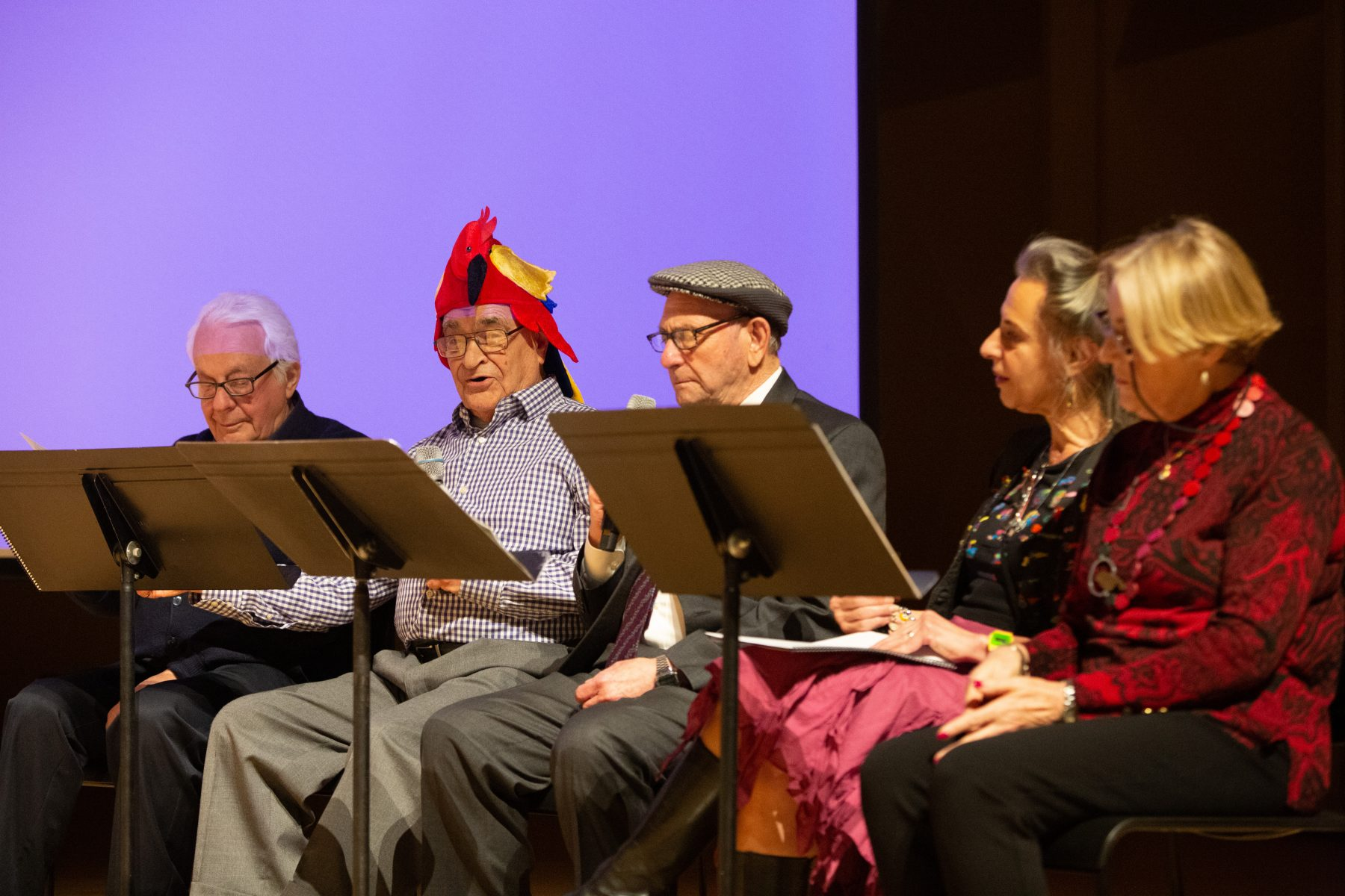 Members of the Ladineros group, including one man wearing a parrot hat, read from scripts