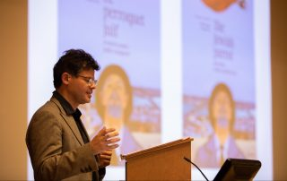 "François Azar, wearing a cardigan, button0up shirt, and glasses, speaks at a podium, with the colorful front cover of ""The Jewish Parrot"" projected in the background"