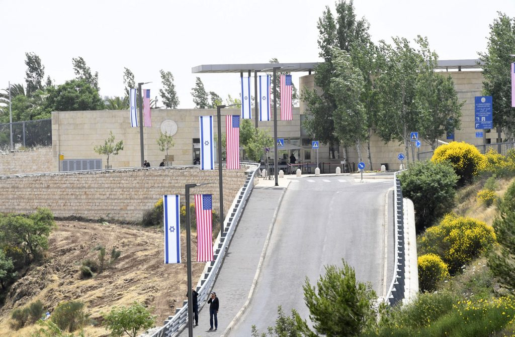 A road lined with posts bearing the United States and Israeli flags leads to a light stone building surrounded by desert trees