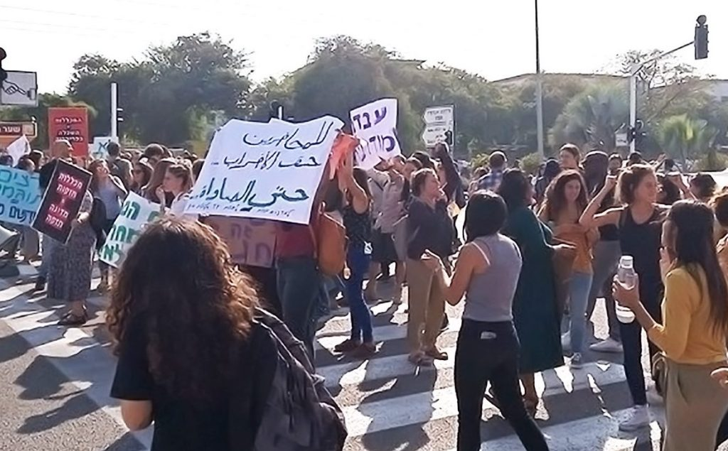 Students stand in a crosswalk holding up signs in Hebrew and Arabic