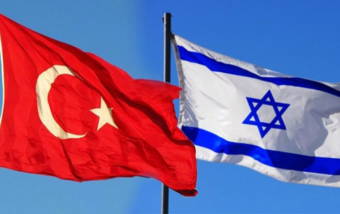The red Turkish flag showing crescent moon and star flies with the white Israeli flag with blue stripes and Star of David next to it
