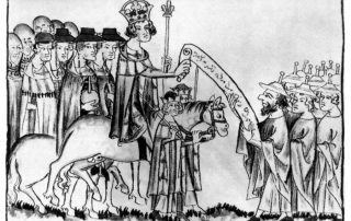 Black and white print shows a king with crown, robes, and scepter riding a horse, flanked by a robed entourage, handing a scroll covered with script to a group of Jewish men in robes and pointed caps