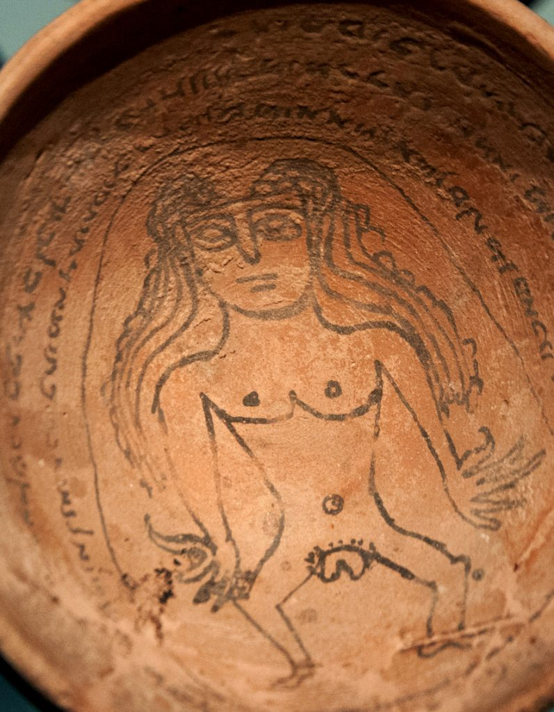A historic bowl that appears to be ceramic, showing the image of a female body with long hair and prominent labia, ringed by Aramaic text