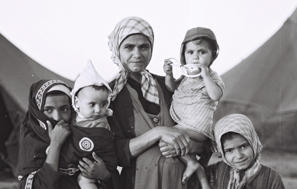 Black-and-white photograph of a woman in a headscarf and long dress holding a baby, with two other girls in scarves and robes, one holding a baby, at her side. Tents are visible in the background.