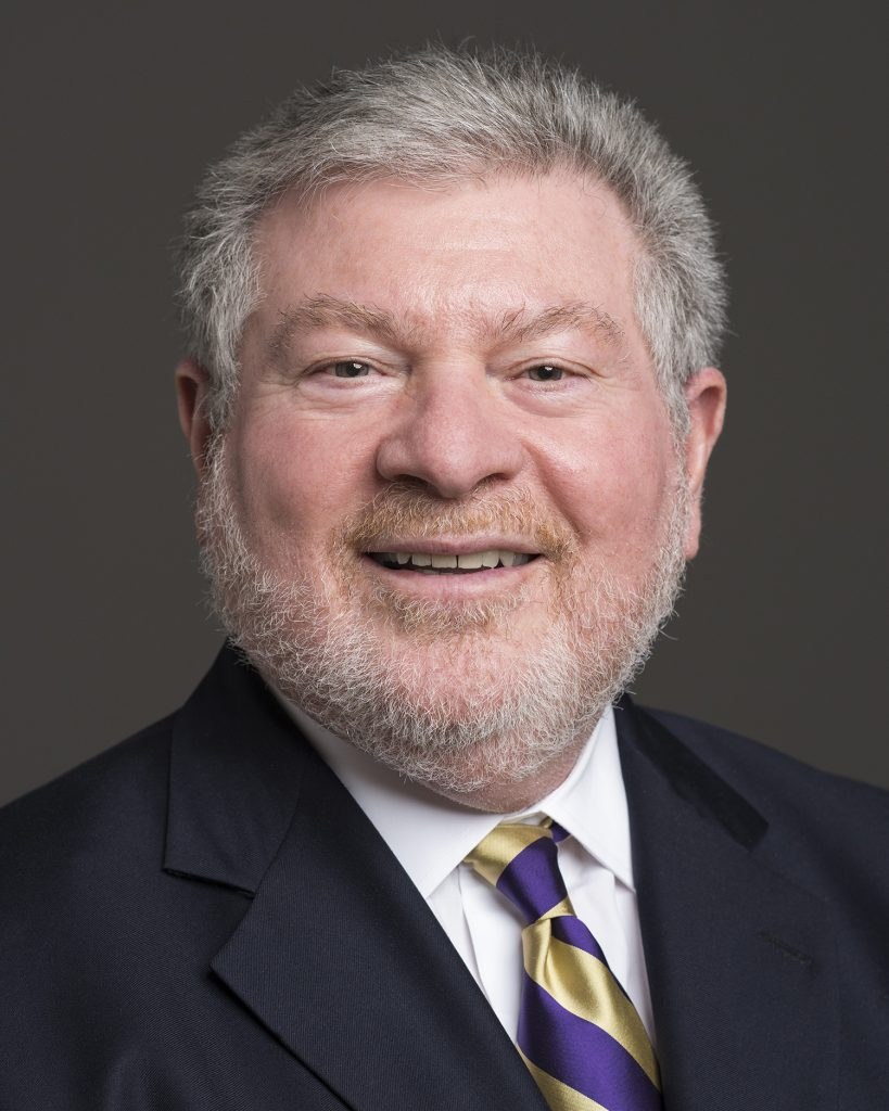 Portrait of Joel Benoliel smiling, wearing suit jacket and purple and gold tie