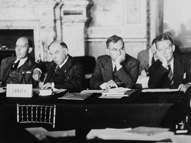 "A black-and-white photograph showing four older men in suits sitting at a long table behind a placard reading ""Canada,"" with papers sitting in front of them"