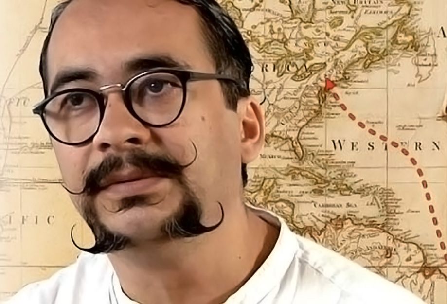 Portrait of Carlos DeMedeiros wearing glasses and a white shirt, with a historic map showing a route from Spain to Latin America