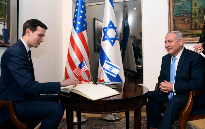 Donald Trump's son-in-law, Jared Kushner, sits across from Israeli Prime Minister Benjamin Netanyahu in an official office where the U.S. and Israel's flags are displayed