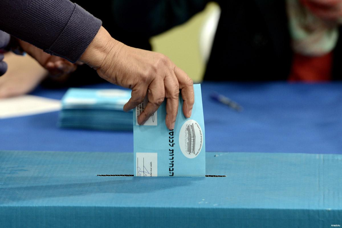 Photograph showing a hand placing a light blue official ballot with Hebrew in a blue dropbox