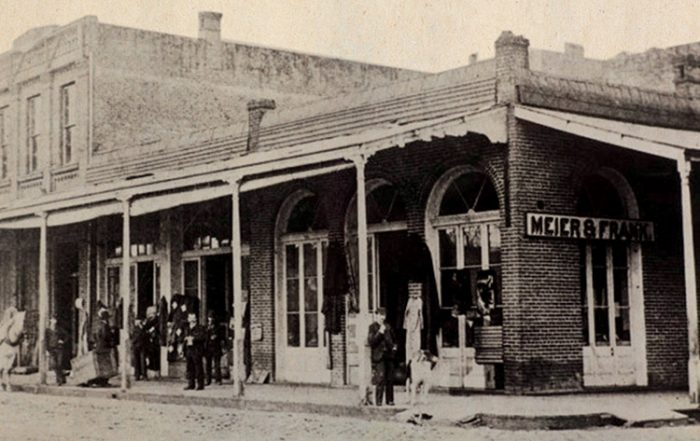 Historic black-and-white photograph shows a wide, shaded storefront from the mid-1800s with a sign in front reading